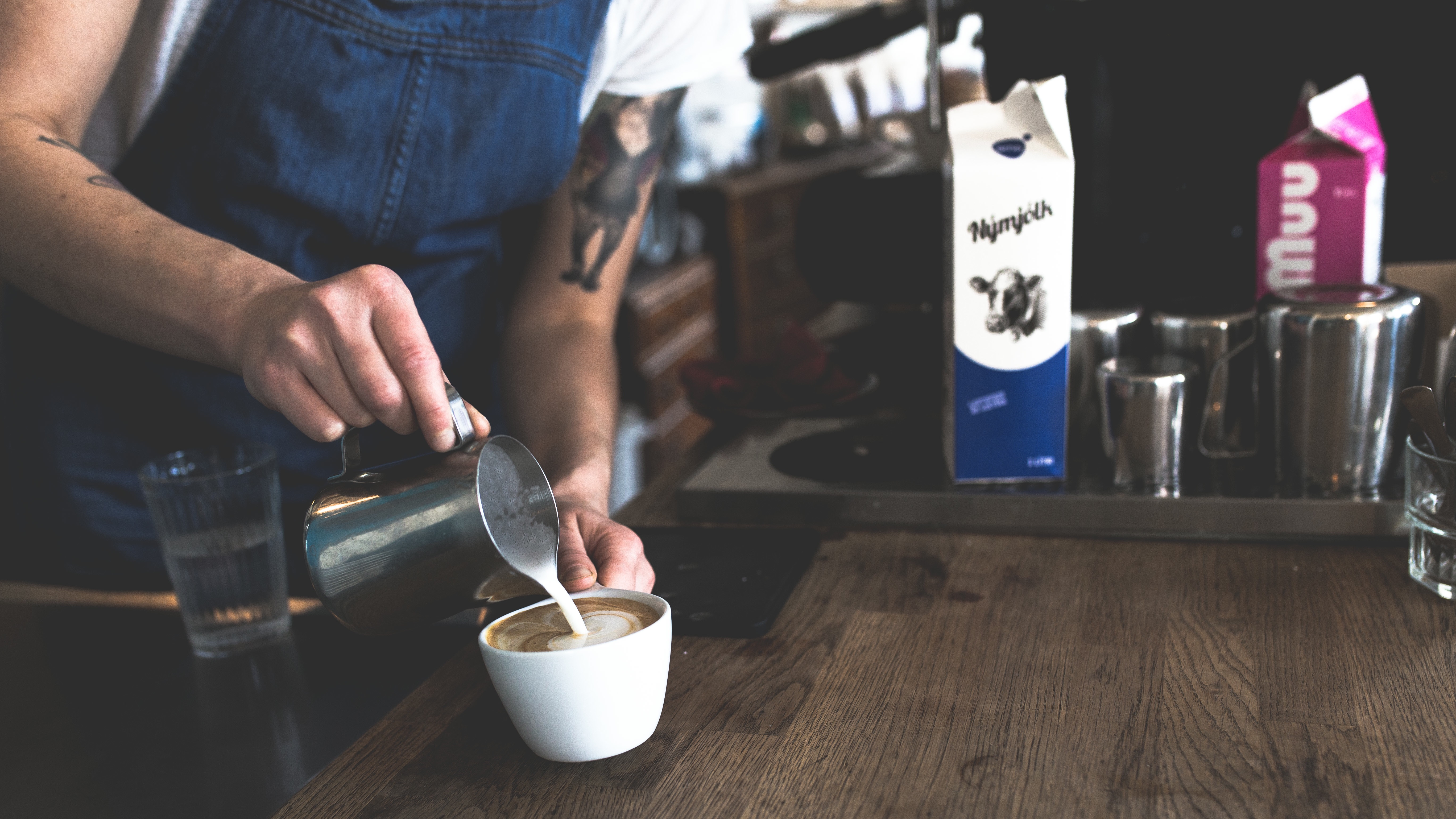 Barista performing job listed in restaurant employee handbook