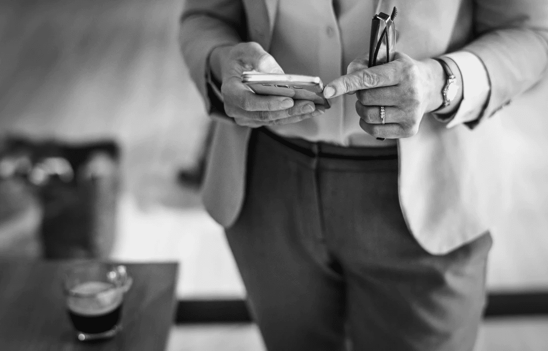 Business owner looking at payroll reports on his mobile device