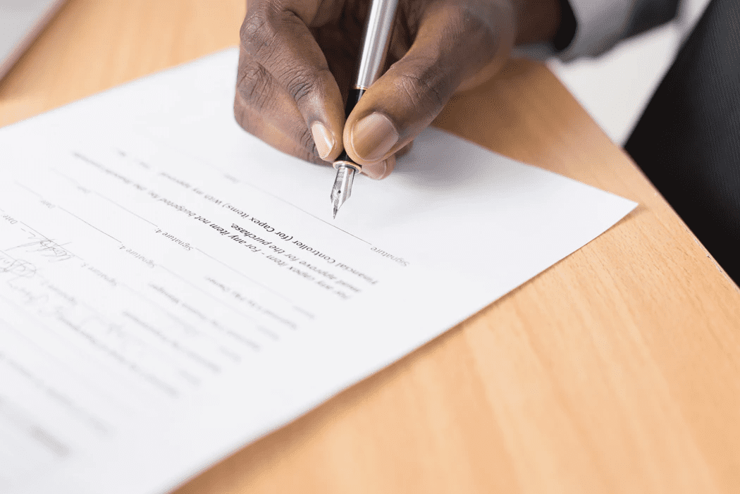 Hand of a manager holding a pen to sign employee discipline form