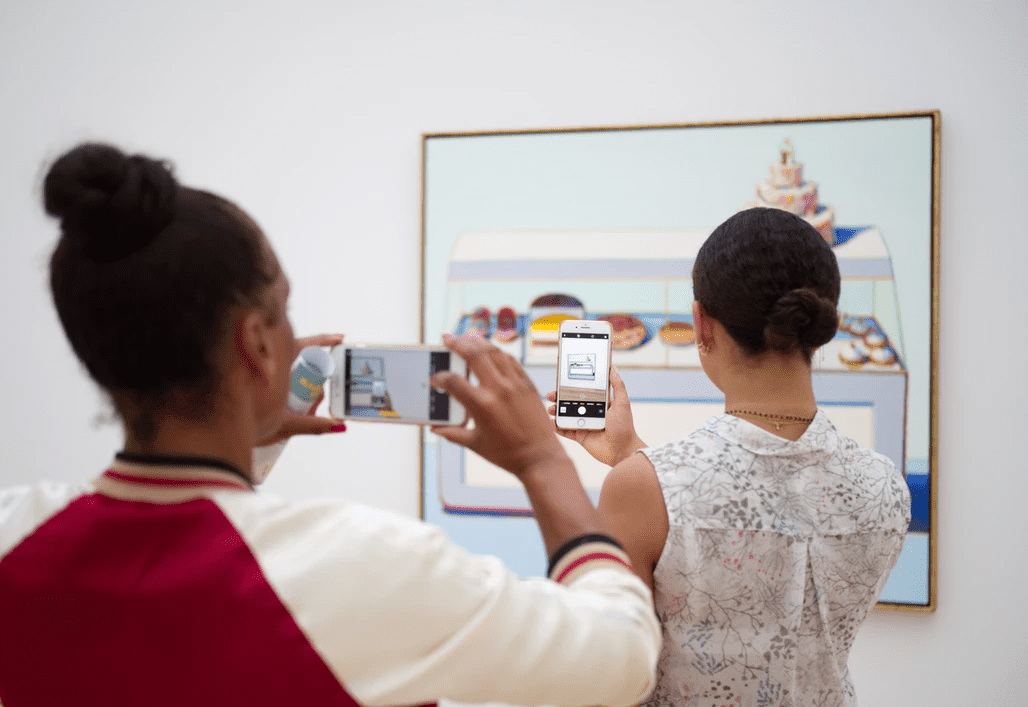 Two women taking photos of a piece of art in a gallery