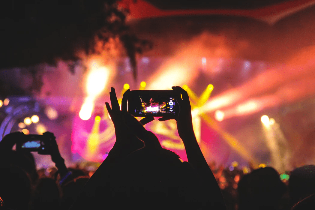 Person recording a concert with her phone in a crowd