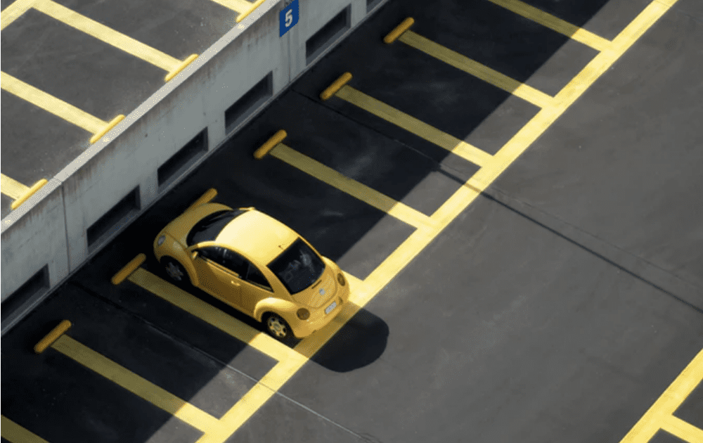 empty parking lot except for a yellow VW Beetle