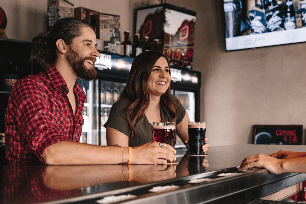Man and woman drinking beer and discussing owning a bar
