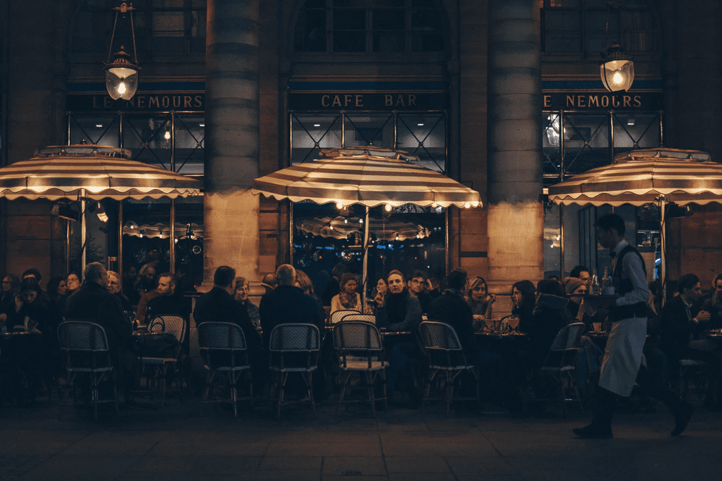 patrons eating outdoors in front of a cafe at night
