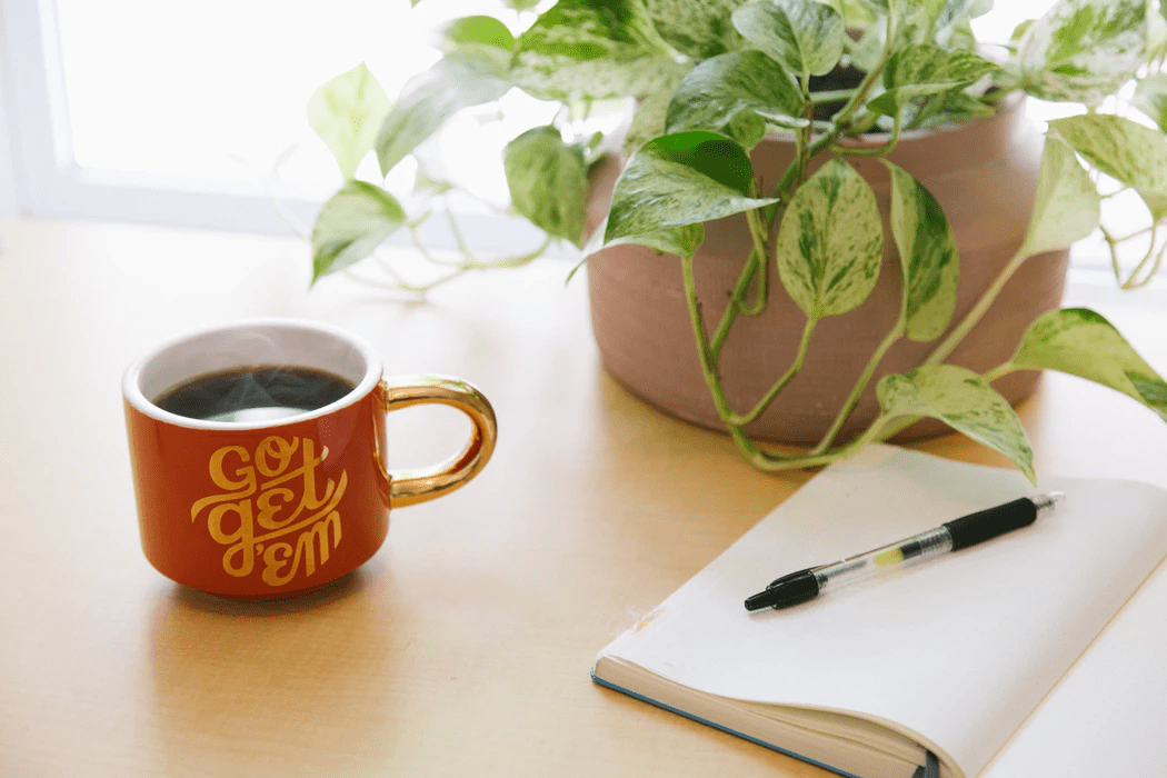 Coffee mug with positive attitude phrase, plant, and notebook with pen on wooden desk