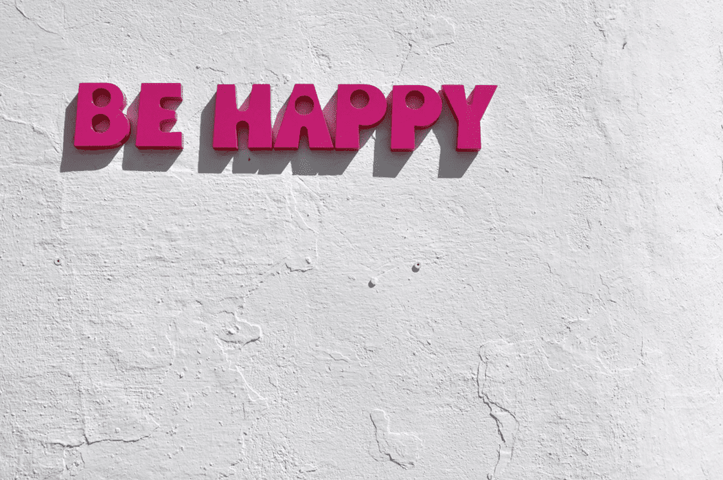 """""""Be Happy"""" sign on concrete wall to promote positive attitidues"""