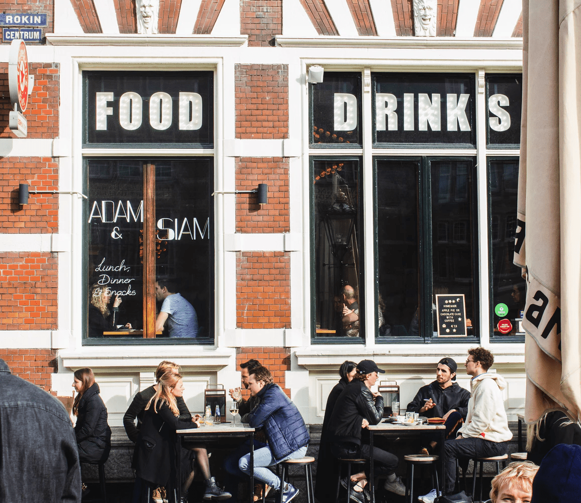People dining outside of a restaurant in front of the windows