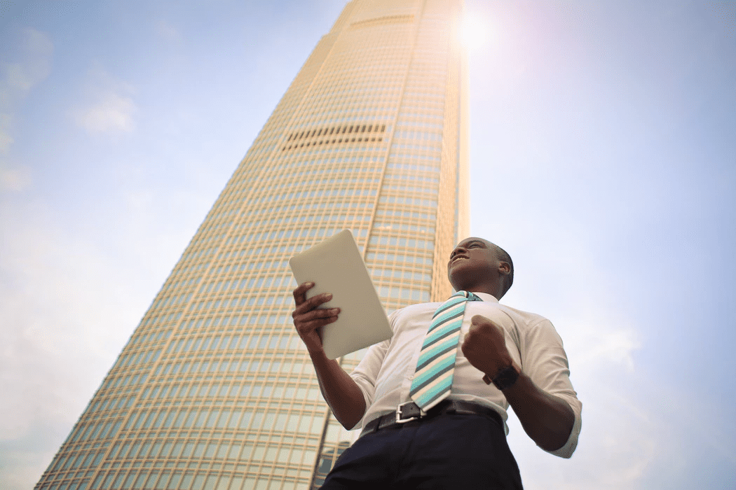 Business owner standing outside a tall building, celebrating success with workforce optimization