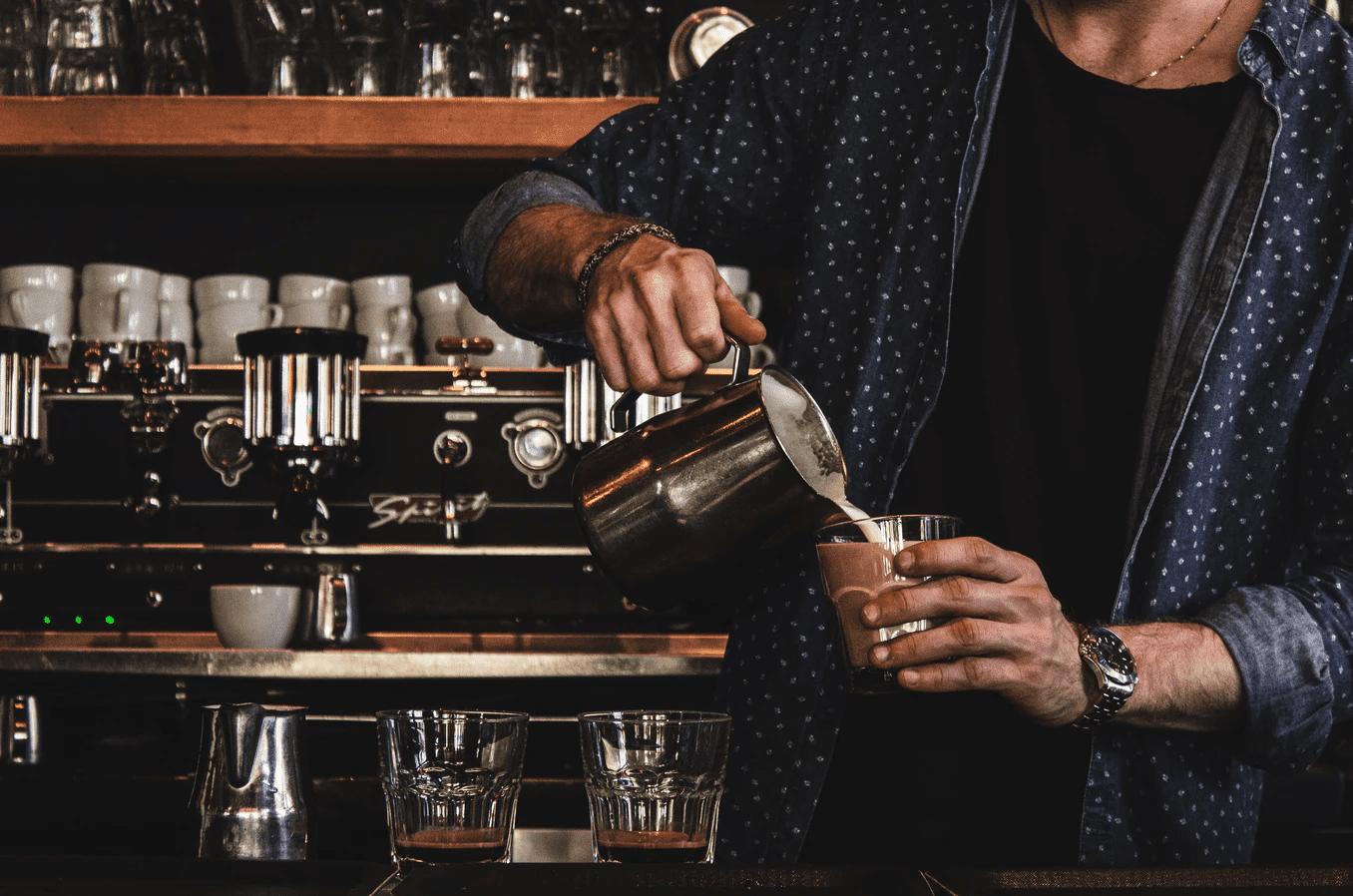 Barista pouring cream in coffee