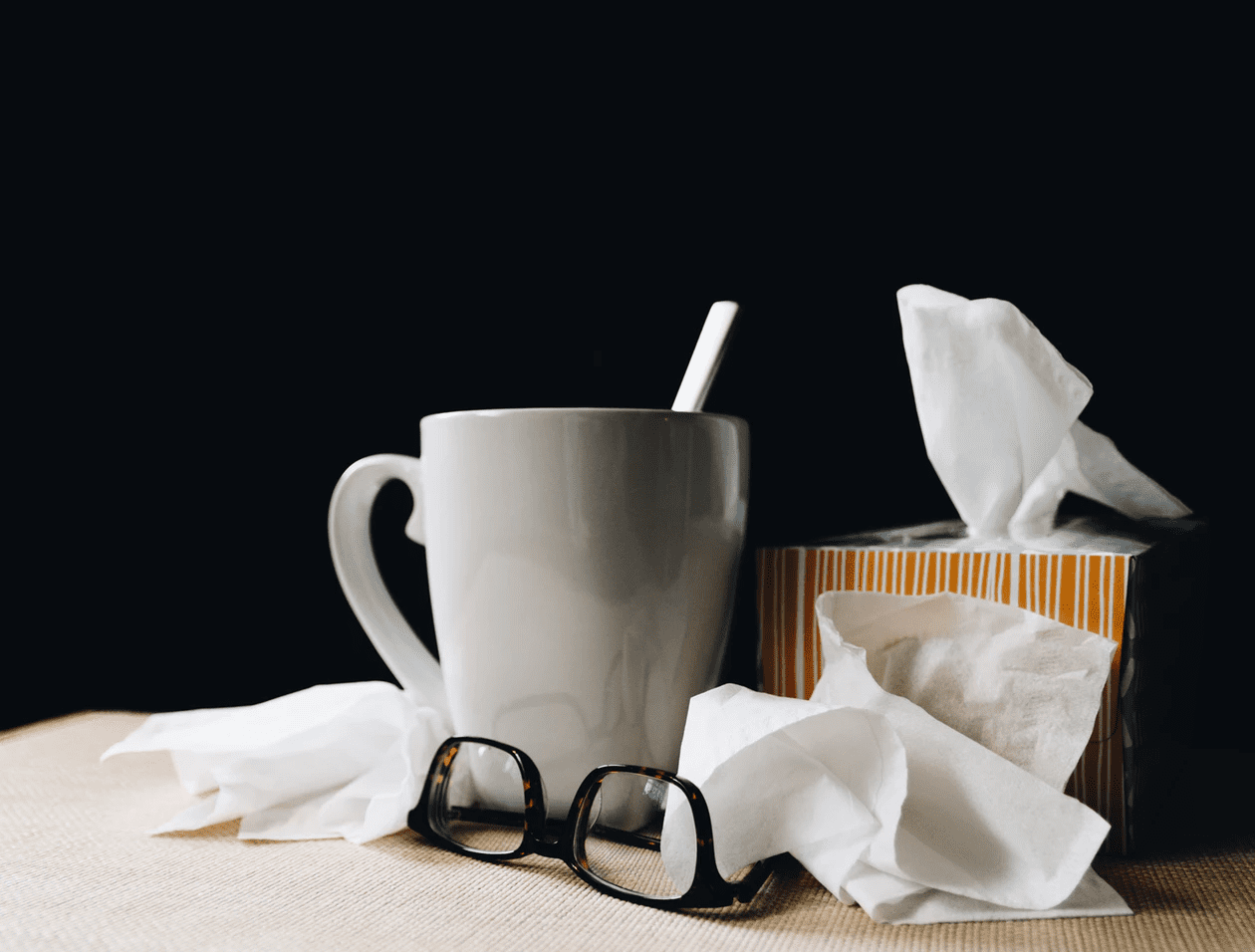 Mug, glasses, and tissues on a table