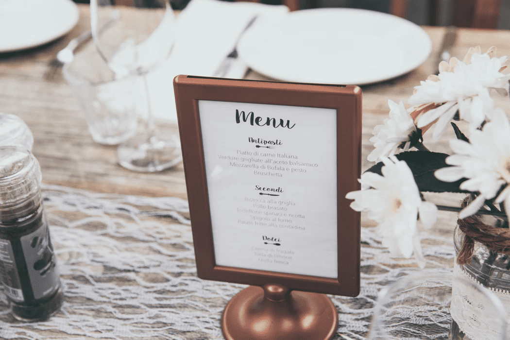 restaurant menu in a stand on fancy table with lace cloth and white flowers