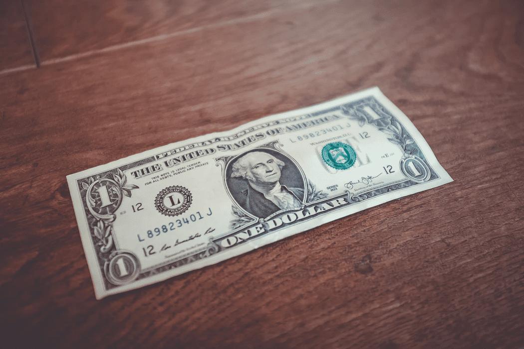 Dollar bill on a wooden tabletop