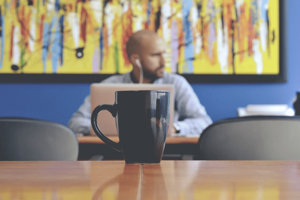 Man in cafe on his laptop with coffee mug on the table in front of him