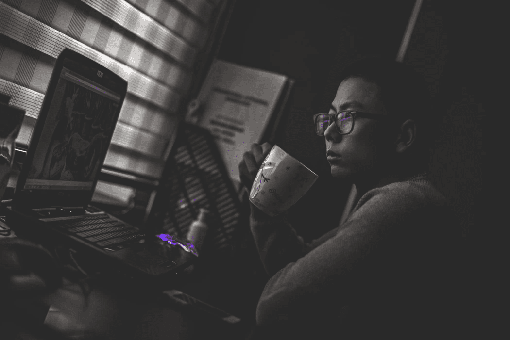 Manager drinking coffee and looking at his laptop, contemplating employee satisfaction