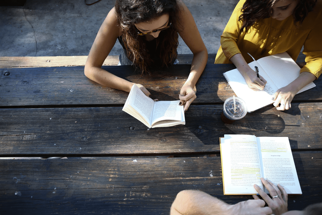 3 women sitting together outside at a picnic table journaling and reading