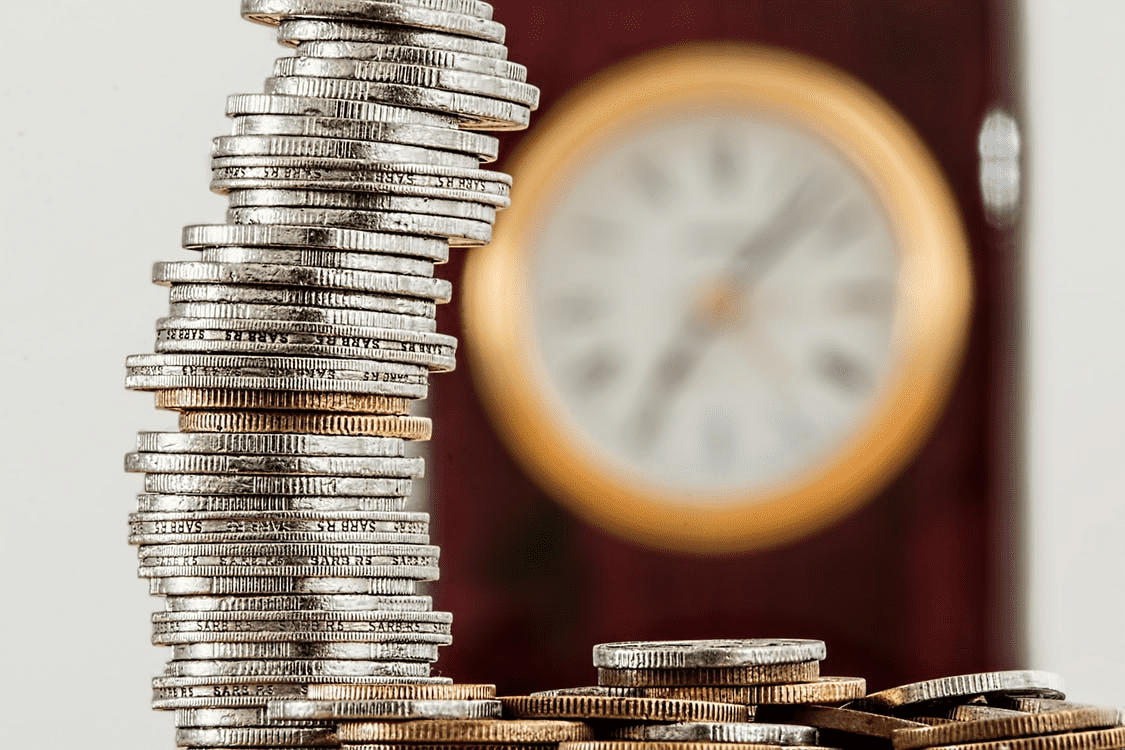 coins stacked high with clock in the background