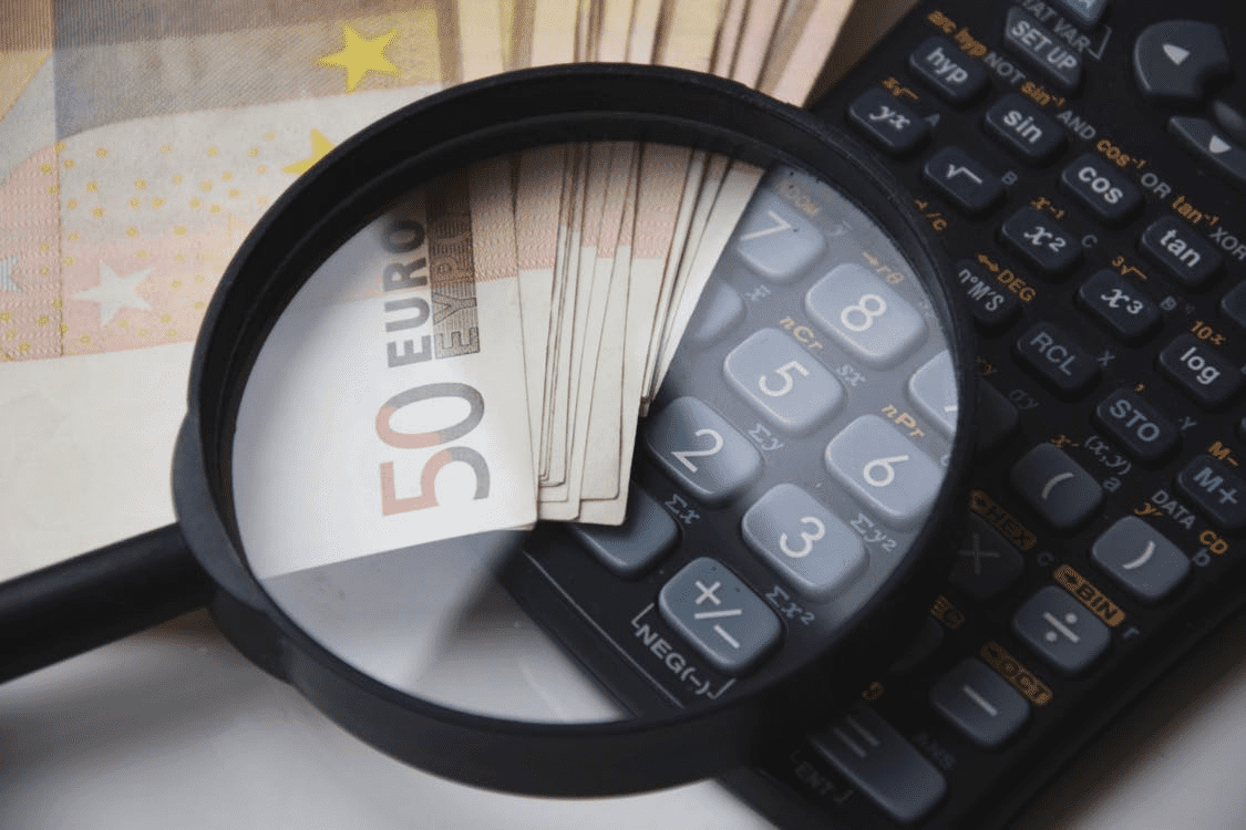 magnifying glass, money, calculator for figuring out PTO accrual