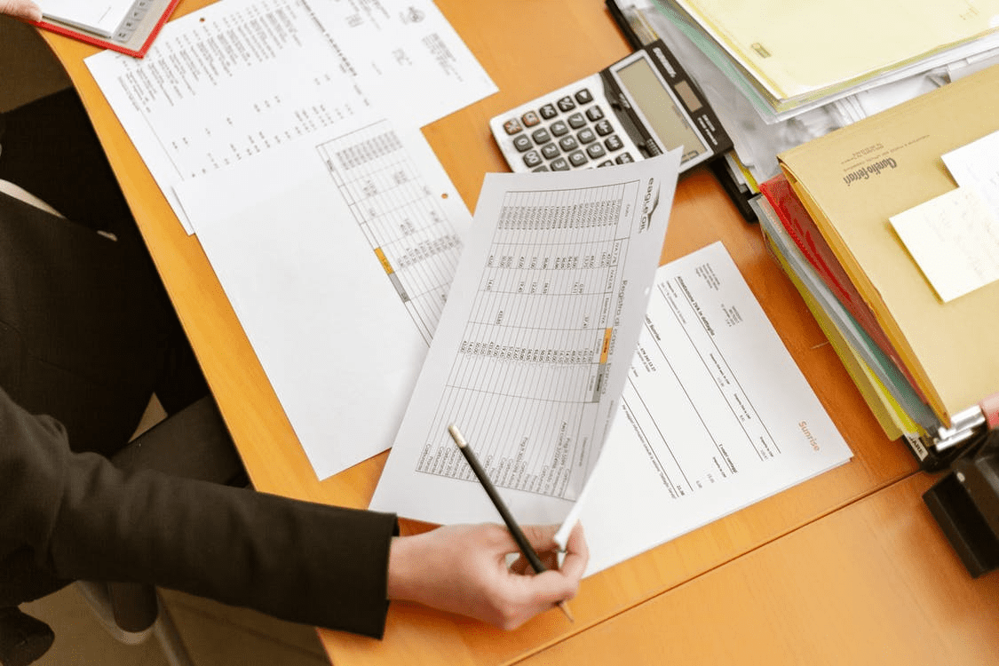 Business owner calculating PTO accrual at her desk with spreadsheets and calculator