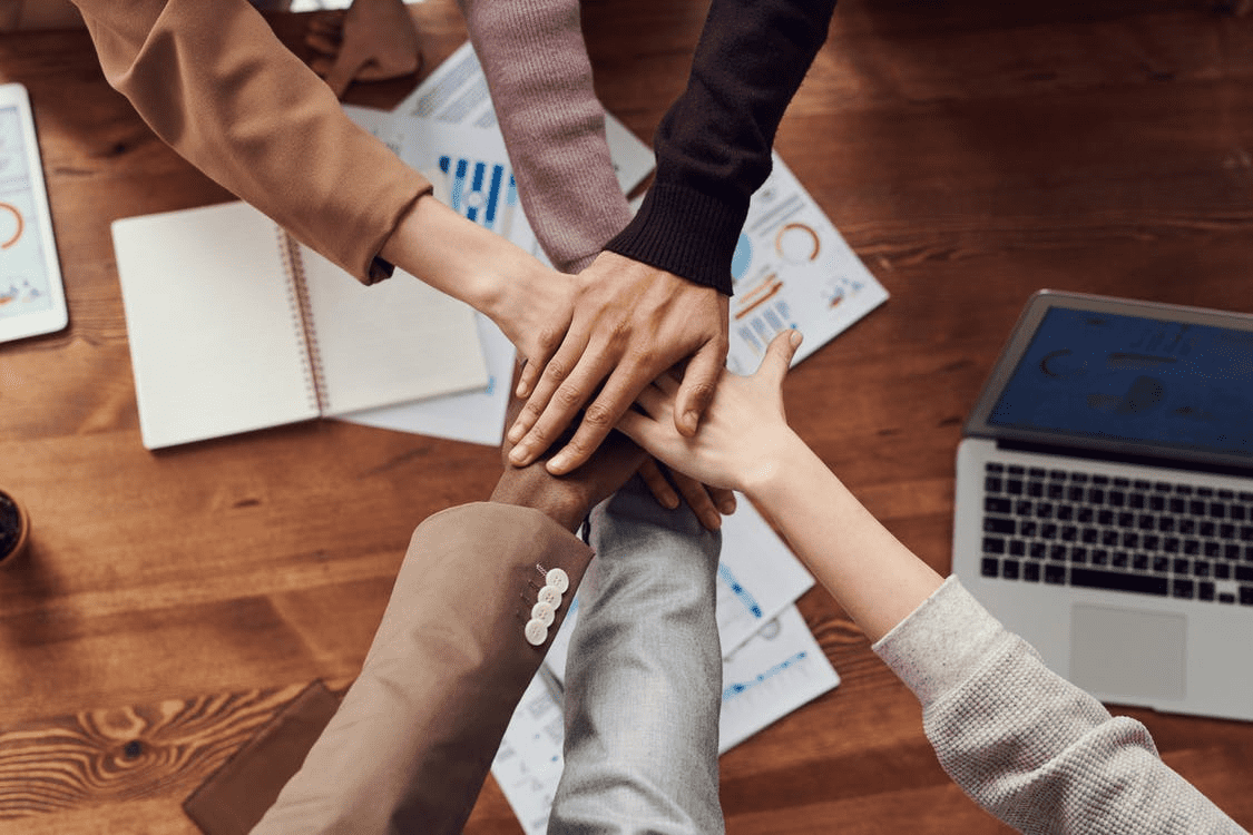 Coworkers putting their hands together in support of supplier relationship management