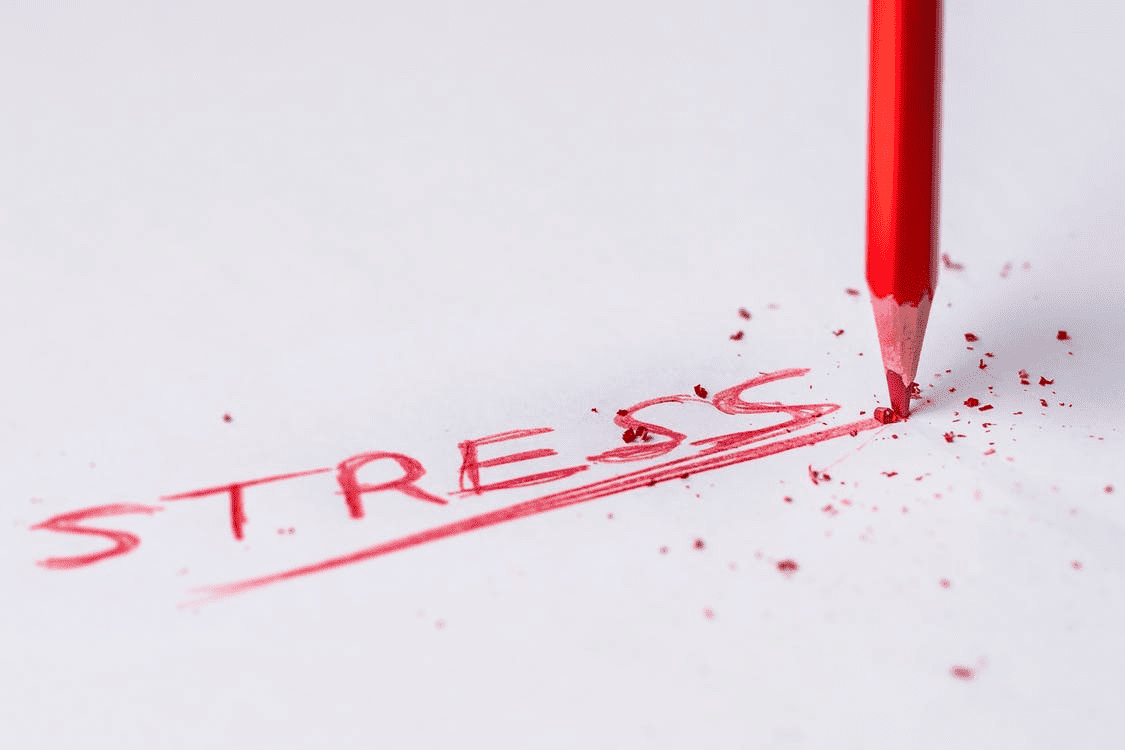 """the word """"stress"""" being written with a red pencil"""