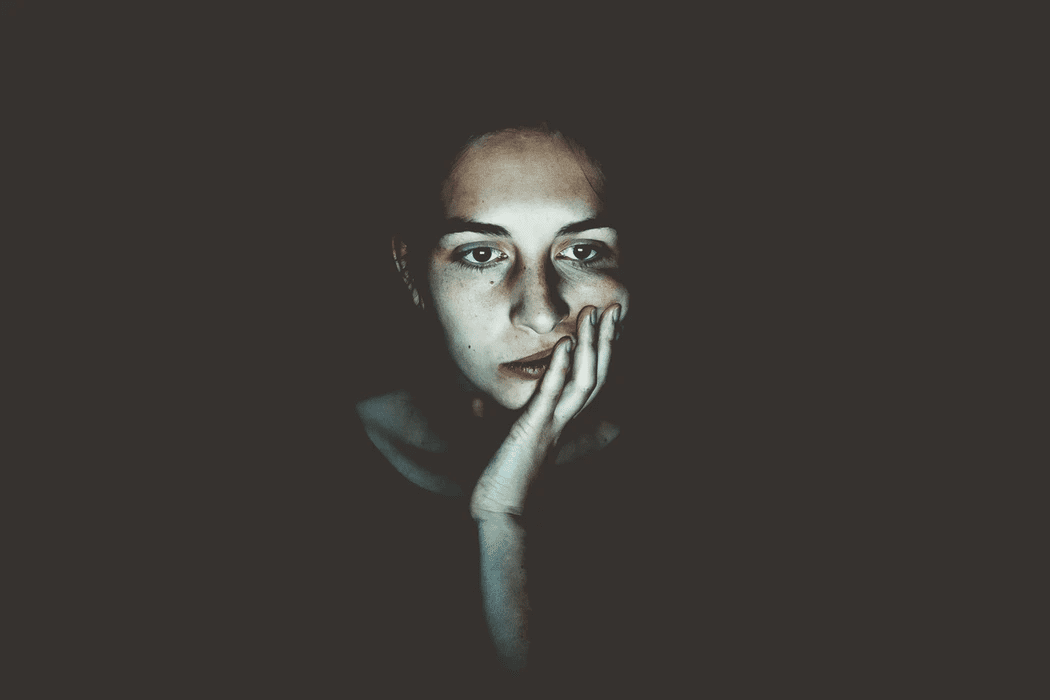 Woman with her face in her hand in a dark background