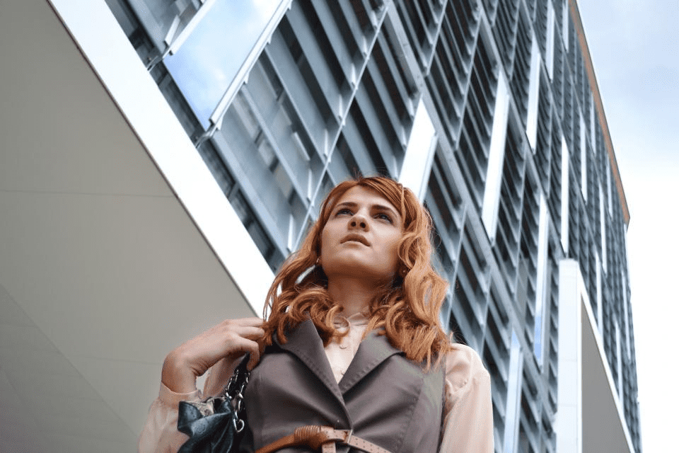 woman walking in front of an office building thinking about starting a small business
