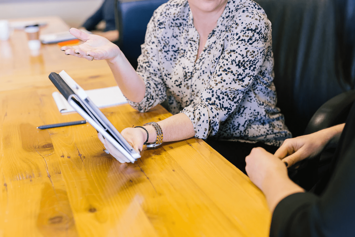 woman giving employee feedback at a wood table with a notepad