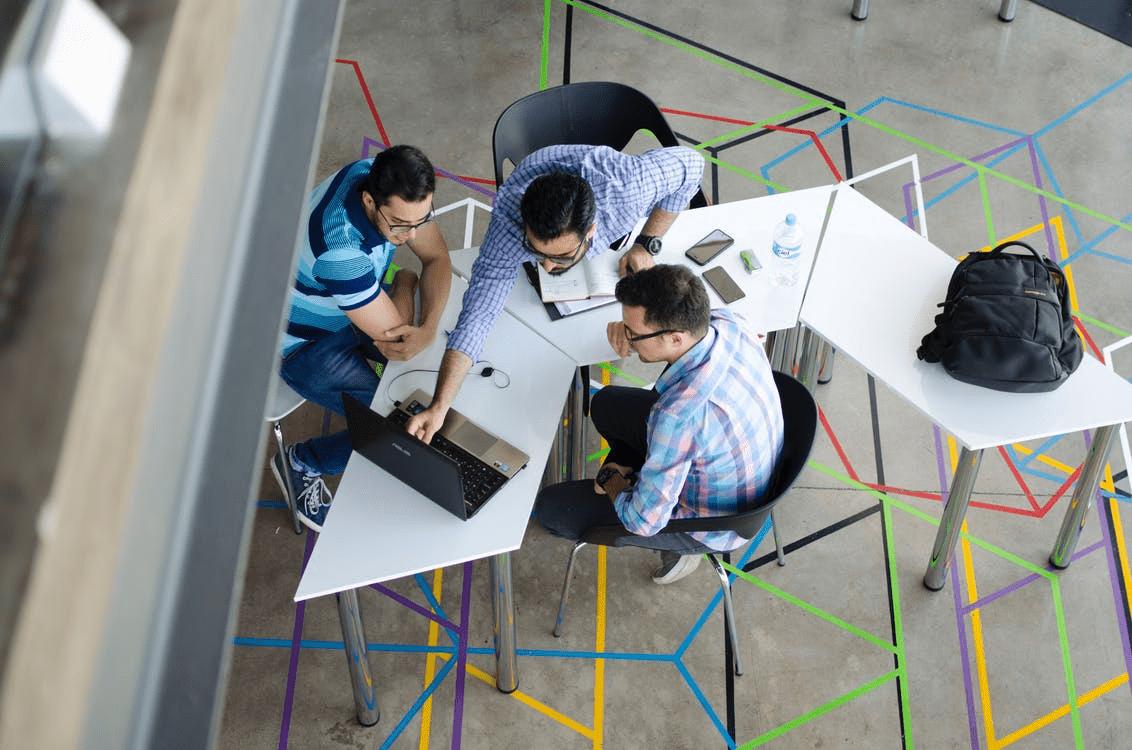 Three entrepreneurs discussing team-building games around a laptop