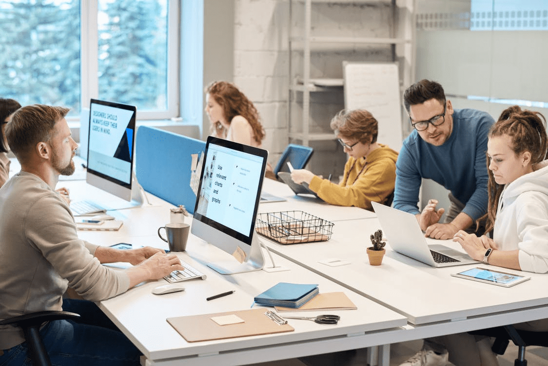 group of high-potential employees working on computers at shared desks