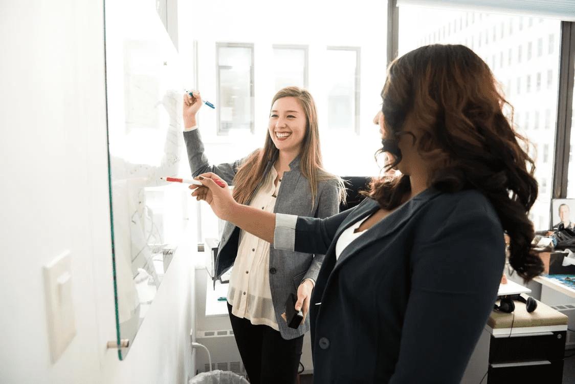 two women entrepreneurs working at a whiteboard