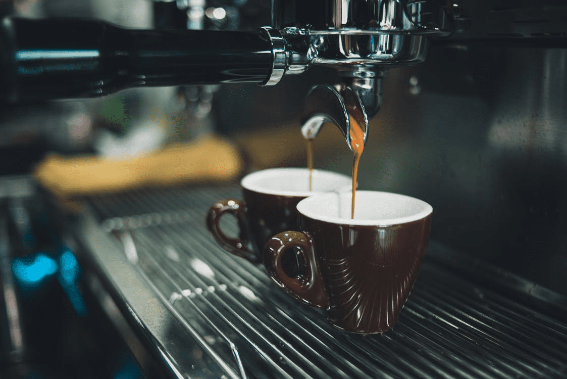 coffee being made in two brown mugs