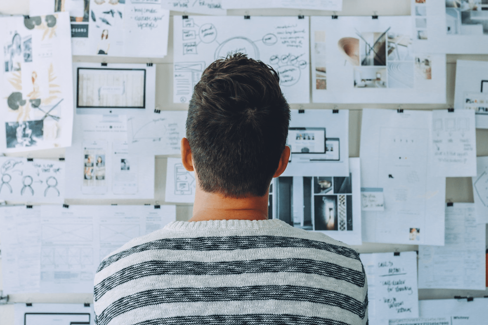 man staring at bulletin board of charts and graphs