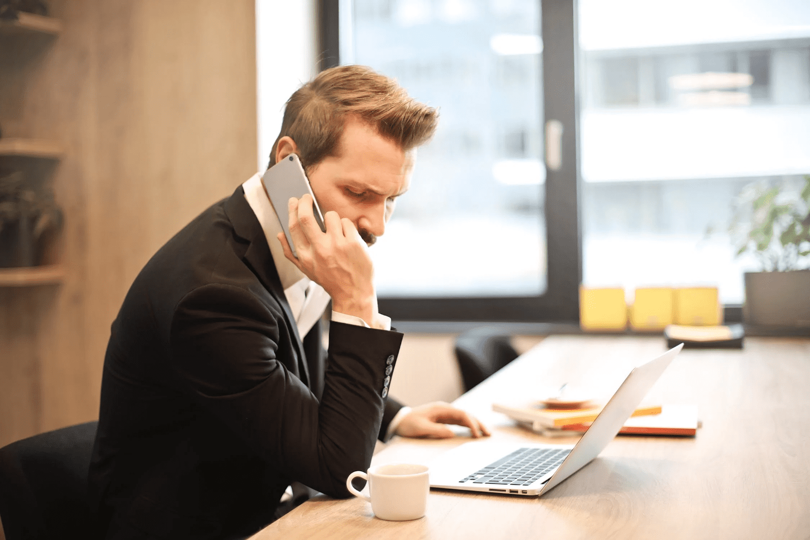 man talking on his cell phone at a conference table