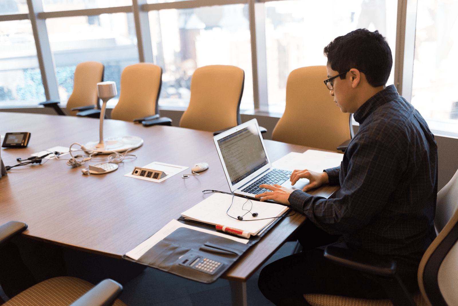 man preparing for virtual meeting in a conference room
