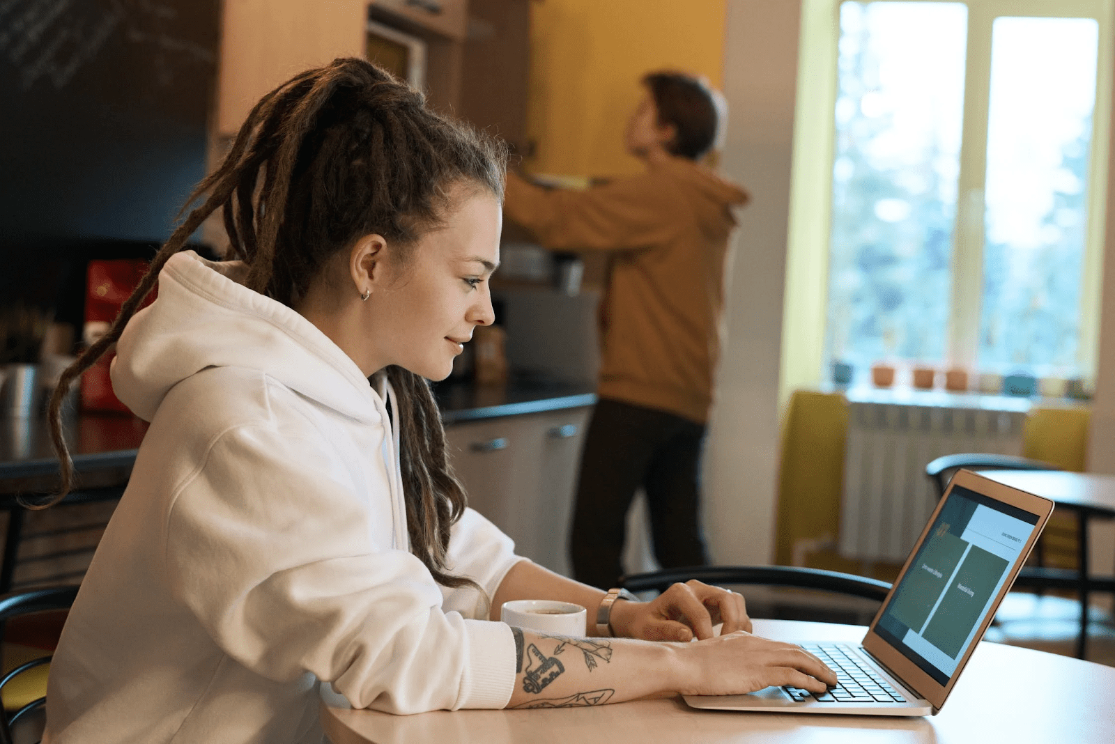 Woman working from home in her kitchen while her husband cooks