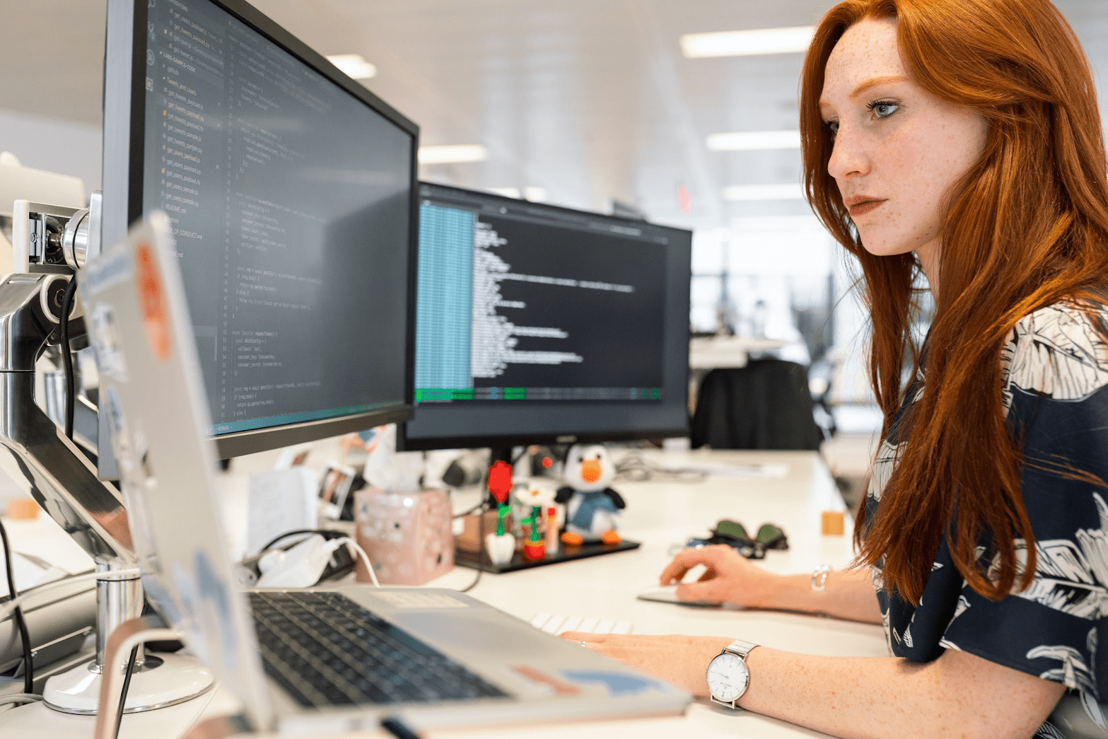 woman in front of two computer monitors creating code of conduct