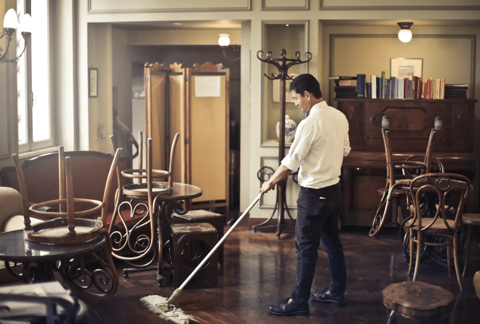 Man practicing how to clean a restaurant with a mop