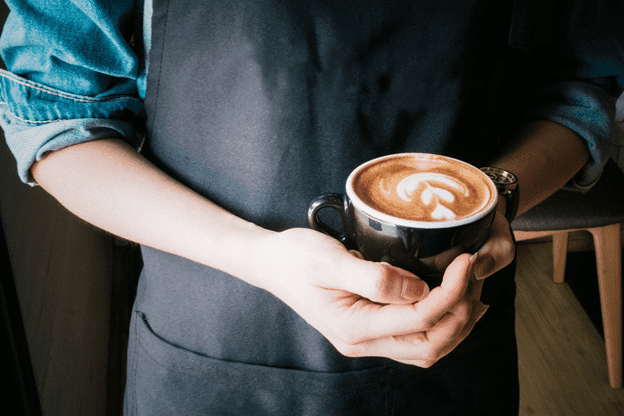 barista holding a cup of coffee