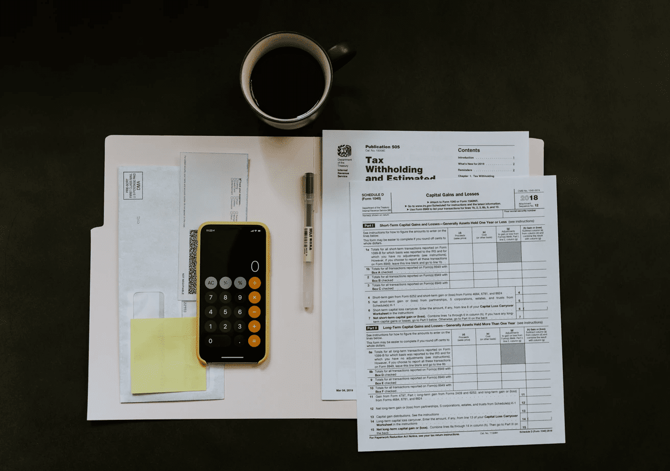 Tax forms with cell phone and coffee on desk