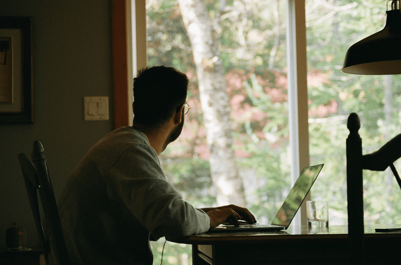 man working remotely looking out his window