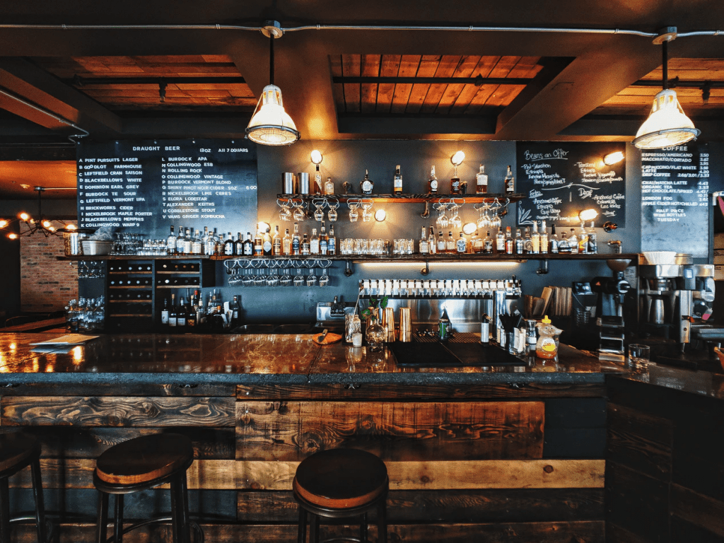 Inside a rustic bar with wood bar top and bar stools