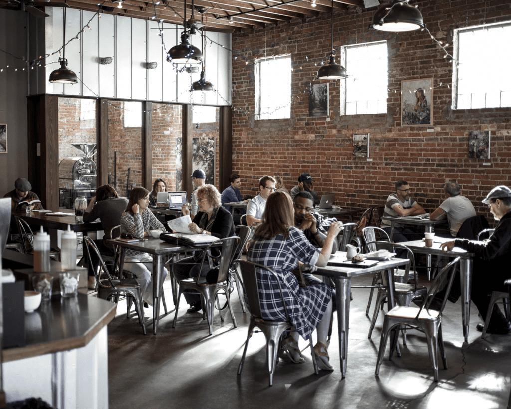 Customers enjoying breakfast in a restaurant with brick walls
