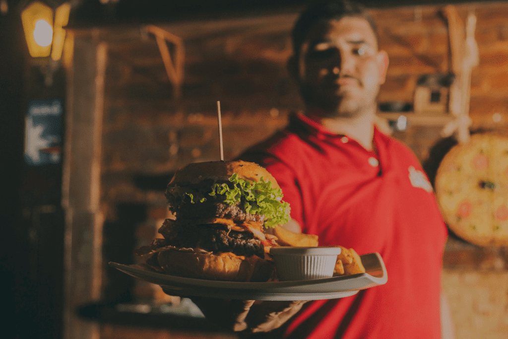 Server holding a double burger and fries