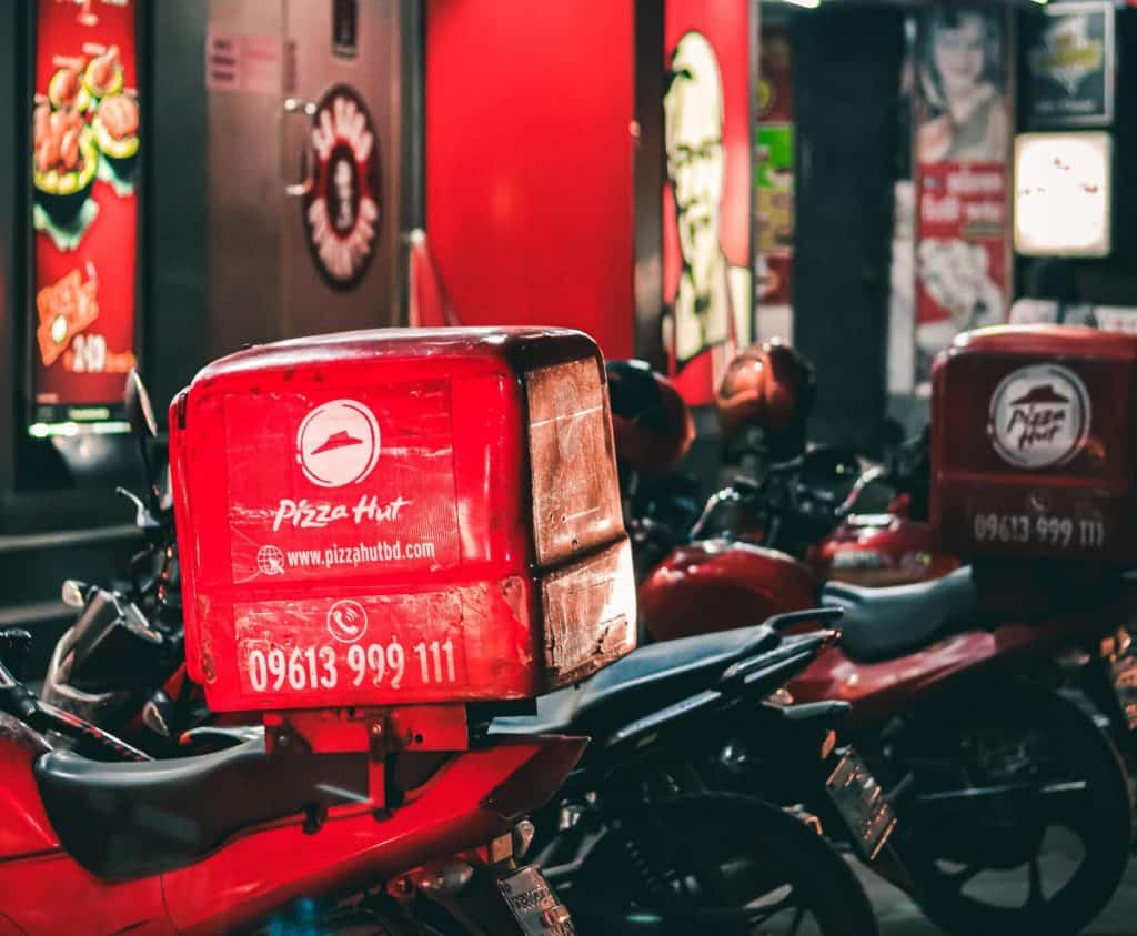 Motorcycle with a pizza hut heat box for delivery services to help with the gig economy