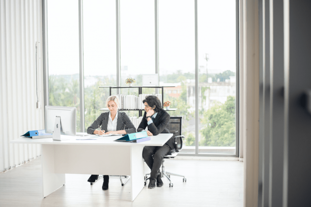 Two workers in an office discussing the gig economy