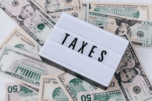 Taxes sign in front of a pile of cash