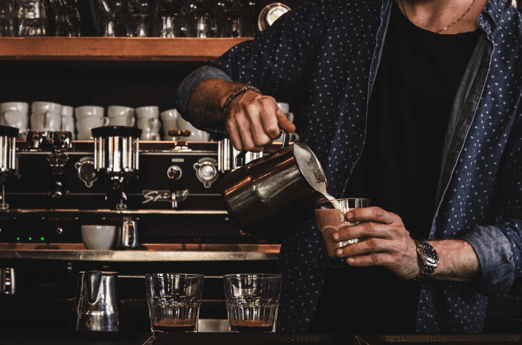 Contingent worker barista pouring cream in coffee