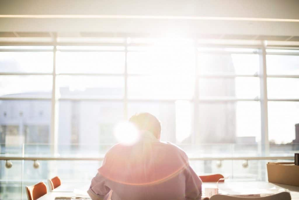 Man sitting in office building in front of window with sun shinning through