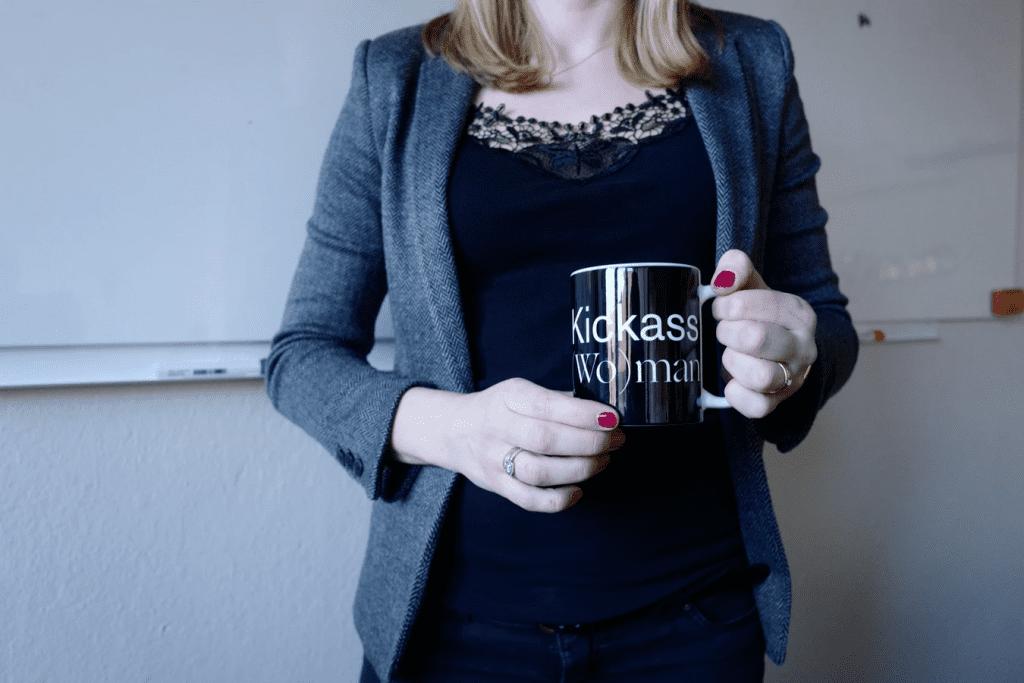 charismatic leadership who is holding a coffee mug that says Kickass Woman