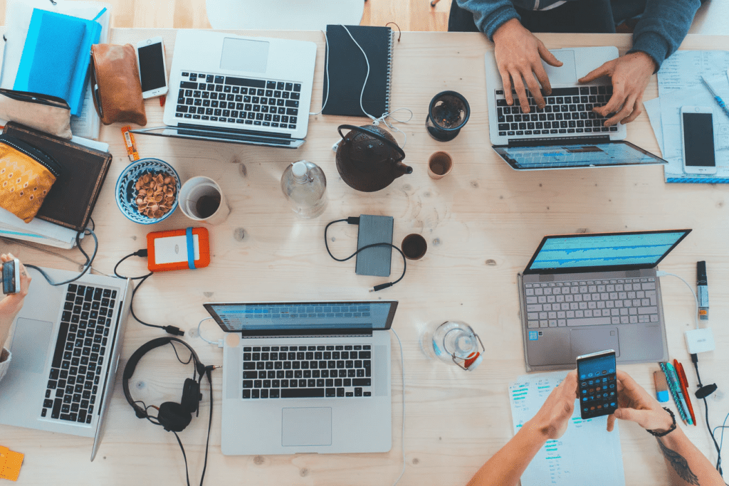 A table filled with BYOD like laptops, cellphones, and tablets that employees are working on